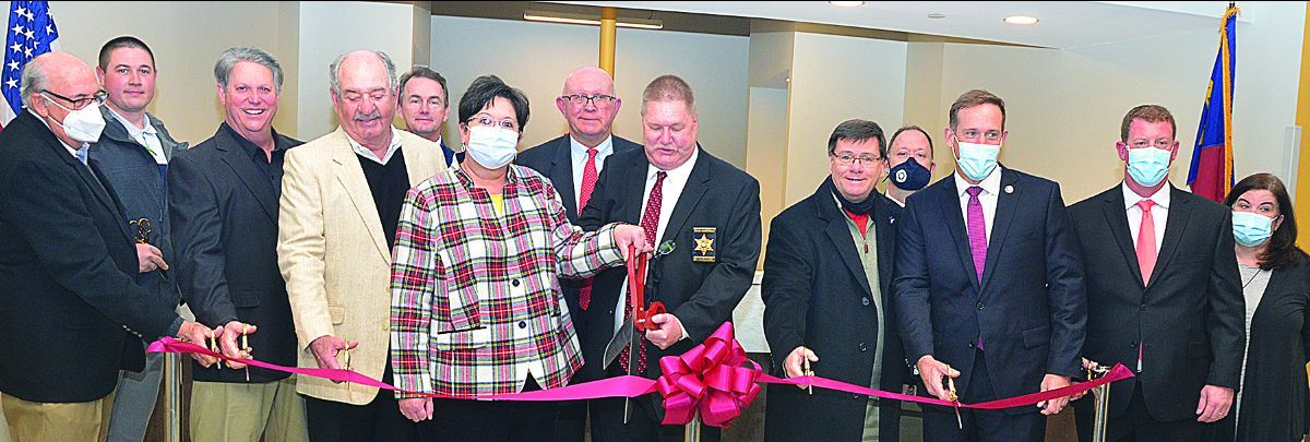 staff cutting ribbon in lobby of new facility