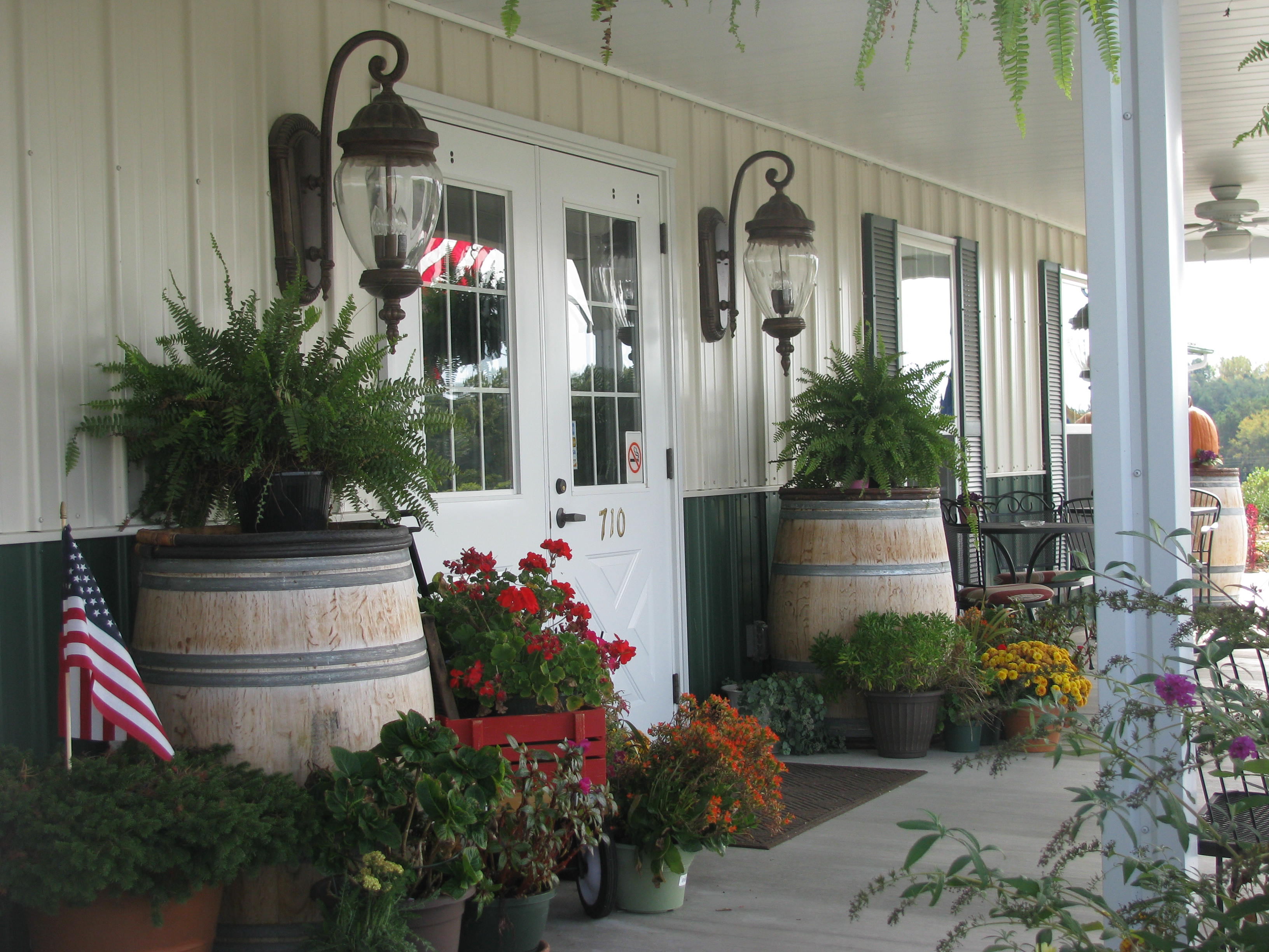 Building with flowers and wine barrels in front
